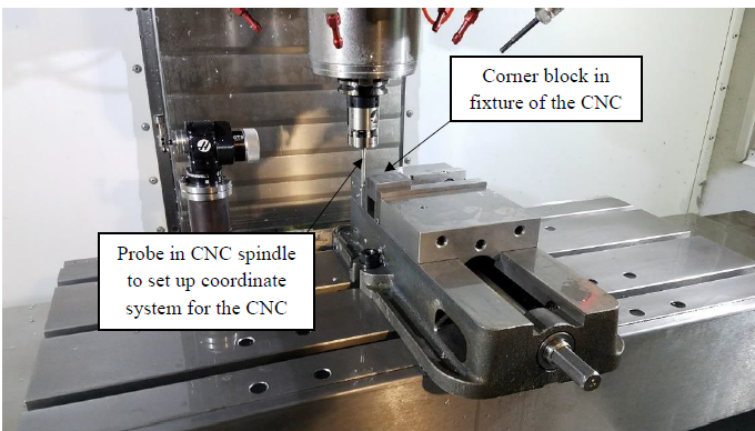 Figure 42. The probe located in the spindle is touching off a corner block in the CNC to give a reference location to perform the drilling operation.